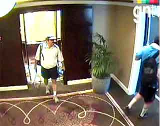Two other alleged members in the hallway outside the victim's hotel room, making a turn to the right while looking to the left, where the victim's room is located.