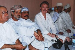 Bob Arno looks up to something as he pretends to relax with men in a souk.