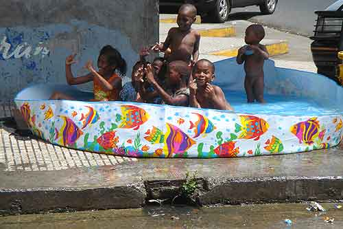 Colon kids cool off in a pool on a street corner.