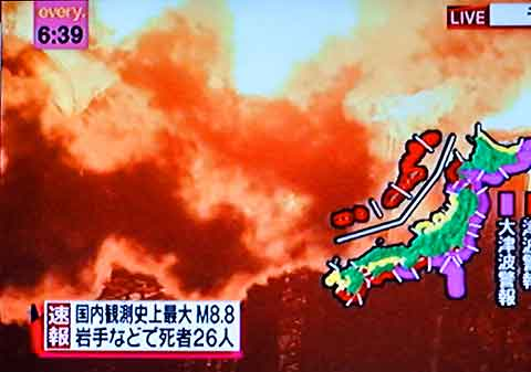 Superimposed on images of fire, a map of Japan shows tsunami warnings in purple.