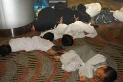 Out cold. Five small boys asleep on the floor of the Dubai airport. An older boy sits off to the right. A girl cuddles against her sleeping mother, in black. Somewhere, there must be an infant, as a baby bottle is standing behind the mother. Eventually the father arrived and squatted over his brood.