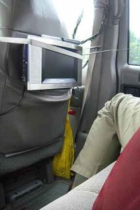 A flat-screen tv is lashed to the back of the seat, its antenna and cable against the window.
