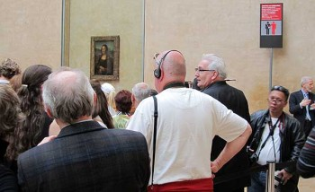 Eiffel Tower pickpockets. A crowd at the Louvre jostle to see the Mona Lisa, ignoring the prominent pickpocket warning.
