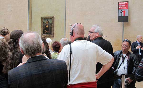 A crowd at the Louvre jostle to see the Mona Lisa, ignoring the prominent pickpocket warning.