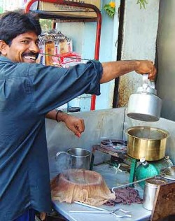 At a tea stall in the Colaba district, the chai-walla pours boiled milk onto tea leaves and spices.