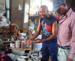 Mondli and Hector purchase herbs from a witchdoctor at a South Africa muti market.