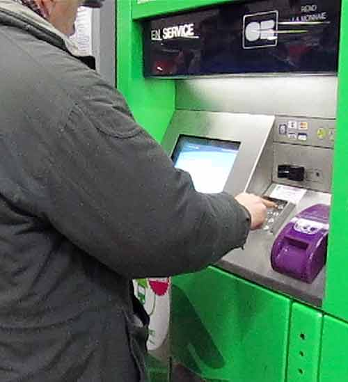 A man enters his PIN while buying Metro tickets with a credit card. shimming