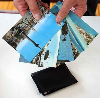 Postcards are offered as if for sale to distracted diners. They're briefly held over a wallet, cell phone, or camera.