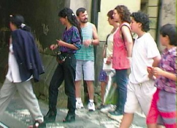 The two women at left are pickpockets. The two boys at right are their stalls. The woman at center was the intended victim.