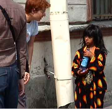 A little gypsy girl begs and gets a bottle of water