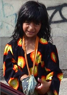 A little beggar girl tucks money into her pouch